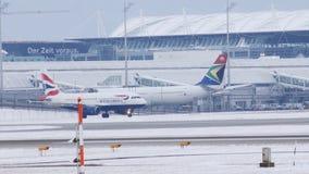 Aviões de jato de British Airways que taxiing no aeroporto de Munich, tempo de inverno vídeos de arquivo