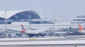Aviões de jato de British Airways que taxiing no aeroporto de Munich, tempo de inverno video estoque