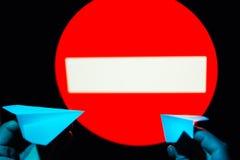 Aviões de papel pequenos da posse dois da mulher nas mãos contra o prohibitin imagens de stock royalty free