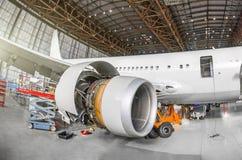 Aviões de passageiro na manutenção do reparo do motor e da fuselagem no hangar do aeroporto Motor do avião da vista imagens de stock