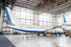 Aviões de passageiro na manutenção do reparo do motor e da fuselagem no hangar do aeroporto Avião da vista completamente de trás  fotos de stock royalty free