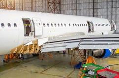 Aviões de passageiro na manutenção, uma ideia da parte traseira da fuselagem no hangar do aeroporto fotos de stock royalty free