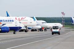 Aviões de várias linhas aéreas e de carro do airdrome Fotos de Stock Royalty Free