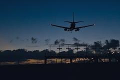 Aviões em cima da aterrissagem na noite Imagem de Stock