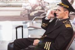 Aviador adulto serio que habla en el teléfono Imagenes de archivo