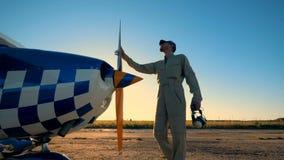 Aviador de sexo masculino que camina a su aeroplano, vista lateral almacen de metraje de vídeo