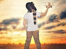 Aviador experimental del ni?o con sue?os del aeroplano de viajar en verano en naturaleza en la puesta del sol foto de archivo