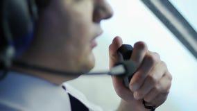 Aviador que habla con el copiloto por el Walkietalkie y que discute los detalles del vuelo metrajes