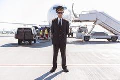 Aviador serio que localiza cerca del avión Imagen de archivo