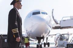 Aviador serio que localiza cerca del avión Imágenes de archivo libres de regalías