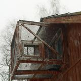 Abandoned aviary for birds. Aviary for birds seemingly abandoned mounted on a house top under snowfall royalty free stock images