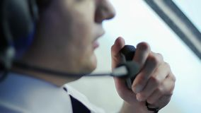 Aviateur parlant au co-pilote par le talkie - walkie et discutant des détails de vol banque de vidéos
