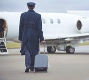 Aviateur se déplaçant à l'avion avec le bagage Photographie stock libre de droits