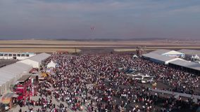 Aviation festival crowd and stunt fighter planes with red and white smoke stock video