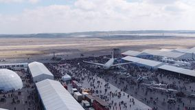 Aviation festival field with crowd and old military aircrafts. Filmed by steady drone from distance stock video footage