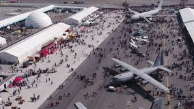 Aviation festival field with crowd and old military aircrafts. Filmed by steady drone from distance stock footage