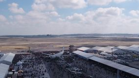 Aviation festival field with crowd old military aircrafts and flying helicopter. Filmed by steady drone from distance stock video