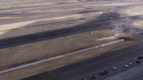 Aviation festival stunt parachute landing aerial view. Filmed by steady drone from distance stock footage