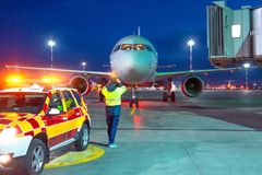 Aviation marshall supervisor meets passenger airplane at the airport at night view. Aircraft is taxiing to the parking place. Ground Crew in the signal vest stock photos