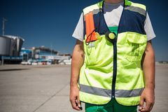 Aviation marshaller in workwear standing at airdrome. Work clothing. Close up of male torso in signaling vest. Airport terminal, runway and blue sky on blurred Stock Image