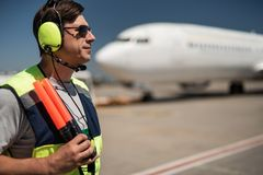 Aviation mechanic in headphones at airport royalty free stock photography