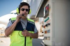 Aviation mechanic holding microphone and portable radio stock photo