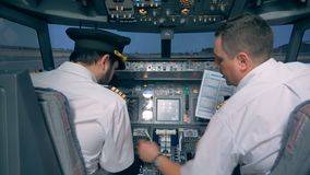 Aviation specialist is instructing another pilot before the flight in the cockpit. 4K stock footage