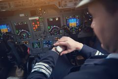 Aviator checking time on arm. Close up male pilot looking at watch while flying plane in cockpit. Job and clock concept Stock Images