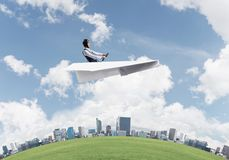 Aviator driving paper plane above business center stock photos