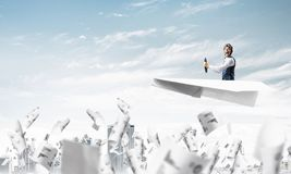 Aviator driving paper plane above business center royalty free stock photos