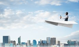 Aviator driving paper plane above business center royalty free stock photography