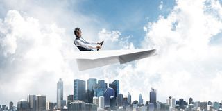 Aviator driving paper plane above business center royalty free stock photo