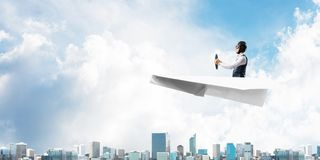 Aviator driving paper plane above business center royalty free stock image