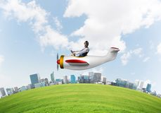 Aviator driving propeller plane above city. Aviator driving propeller plane above business center. Pilot in leather helmet sitting in airplane and holding royalty free stock image