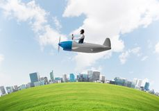 Aviator driving propeller plane above city royalty free stock photos