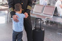 Aviator embracing his small son. After long parting. Little son hugging pilot father. They standing in waiting hall of airport. Focus on kid. Copy space on right royalty free stock photos