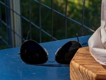 Aviator style sunglasses on table royalty free stock photos