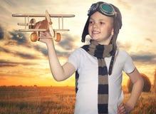 Aviatore pilota del bambino con i sogni dell'aeroplano di viaggio di estate in natura al tramonto fotografie stock