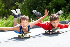 Aviators. Two little boys lying on their skateboards Royalty Free Stock Photos