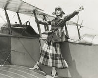 Aviatrix standing on bi-plane