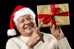 Avid Aged Man Pointing At Golden Wrapped Present. Smiling male pensioner gesturing with his right index finger at a golden wrapped gift raised above eye-level in Stock Photo