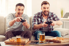 The avid gamers. Two young happy men playing video games while sitting on sofa Stock Images