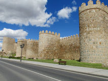 Avila city wall. Medival ancient city wall, battlements, tower, bastion and castle walls of Avila, Spain, around the modern town and buildings, made of yellow Royalty Free Stock Photography