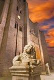 Avila - fasaden av Catedral de Cristo Salvador på skymning och lejonstauten Arkivbilder