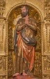 AVILA SPANIEN, APRIL - 19, 2016: Den sned polychrome barocka statyn av St Peter på sidoaltaret i den kyrkliga basilikan de San Vi Arkivbild