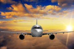 Avião no céu do por do sol Fotografia de Stock