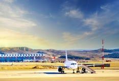 Avion à l'aéroport international moderne de porte terminale au coucher du soleil Images libres de droits