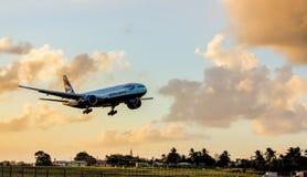 Avion à réaction commercial environ à la terre autour du coucher du soleil en Barbade Image libre de droits