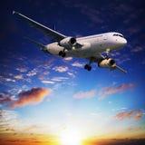 Avion à réaction dans un ciel de coucher du soleil Images libres de droits