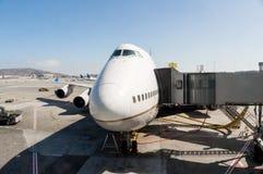 Avion étant entretenu à la porte d'aéroport Images stock
